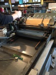 Setting up the letterpress machine before printing.