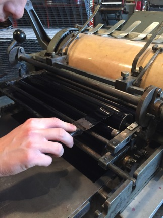 Placing the ink on the roller. You have to be careful not to put too much ink, and also to make sure the ink is evenly distributed on the plate.